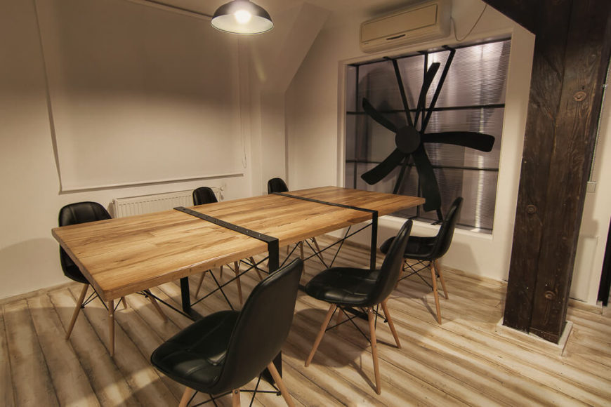 This understated conference room has a large industrial fan built into the wall, furthering the rustic atmosphere.