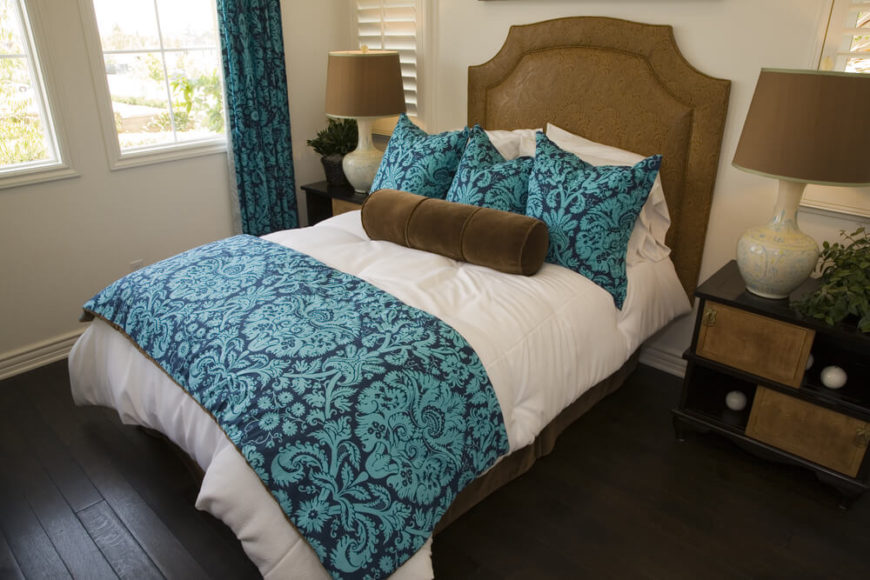 a colorful bed and dark hardwood flooring contrast beautifully in this bedroom the fabric headboard