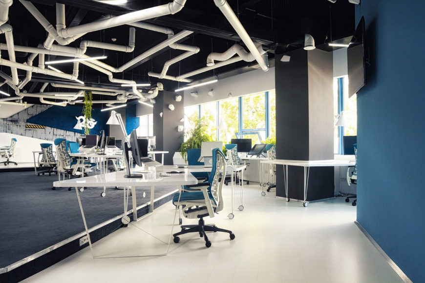 Here we can see the open floor plan of the main office. The polished white desks and floor pair well with the matte blue walls and chairs.