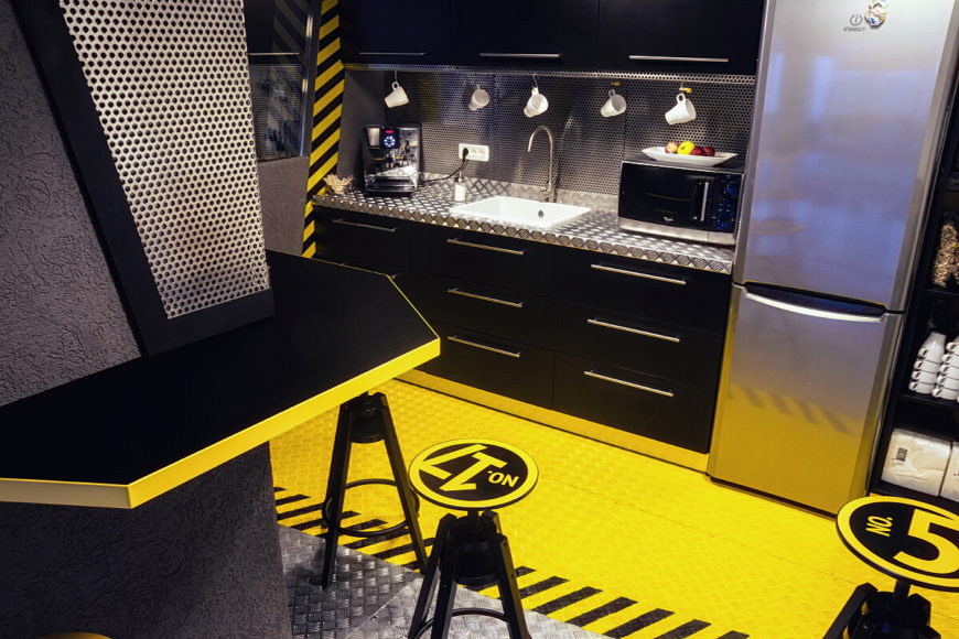 This industrial kitchen is full of bright yellow and metal designs. The room is a whimsical addition that contrasts the theme of the main office.