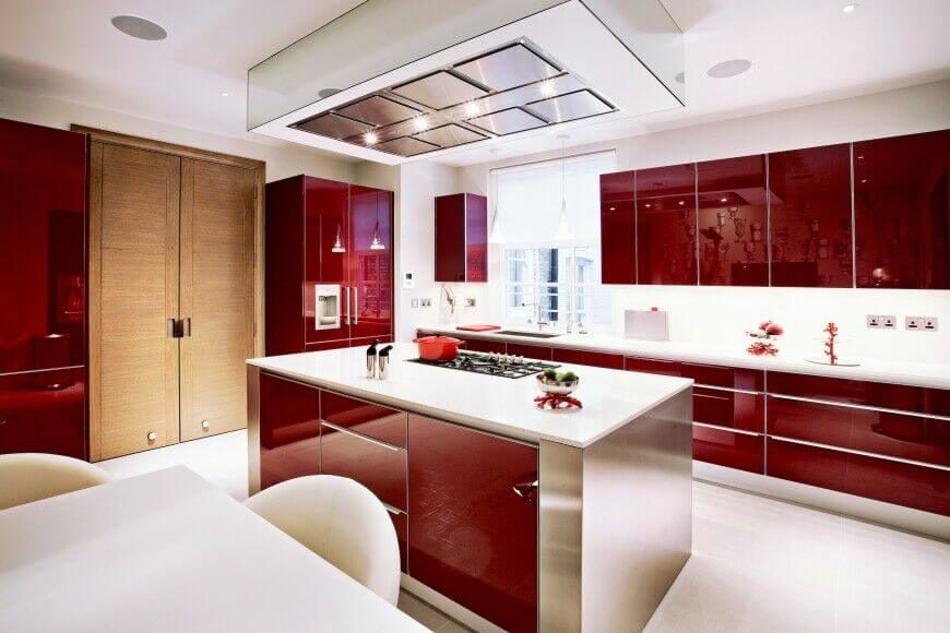 In An Incredibly Sleek And Reflective Modern Kitchen, The White Topped  Island Stands At