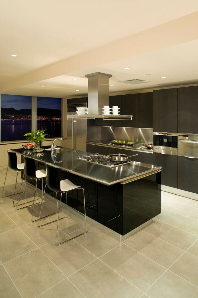 In An Ultra Modern Kitchen Boasting Stainless Steel Countertops And Large  Format Tile Flooring,