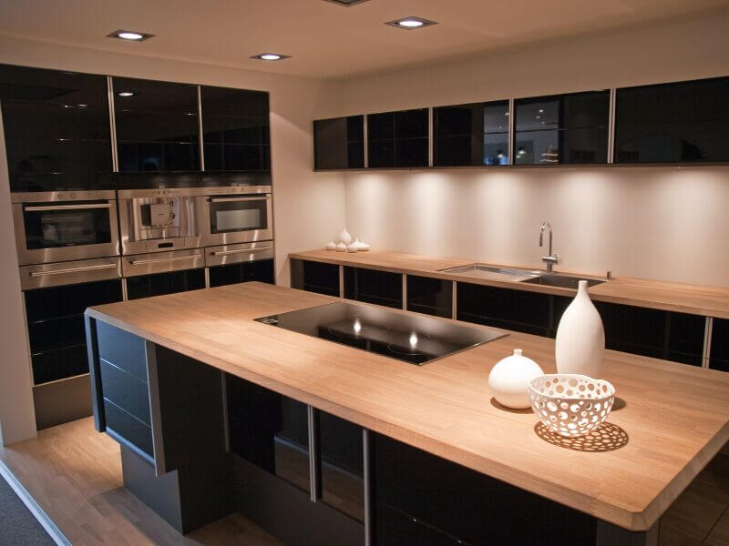 This sleek, high contrast modern kitchen features glossy black cabinetry  juxtaposed against light natural wood
