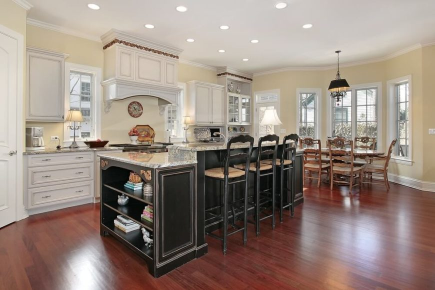 The warm hardwood flooring and white cabinetry of this broadly open kitchen design make an enticing, bright space. The large island in black with light granite countertops stands in stark contrast as a centerpiece element. With a raised tier for dining, and side structure for shelving storage and additional countertop space, it makes the most of its large footprint.