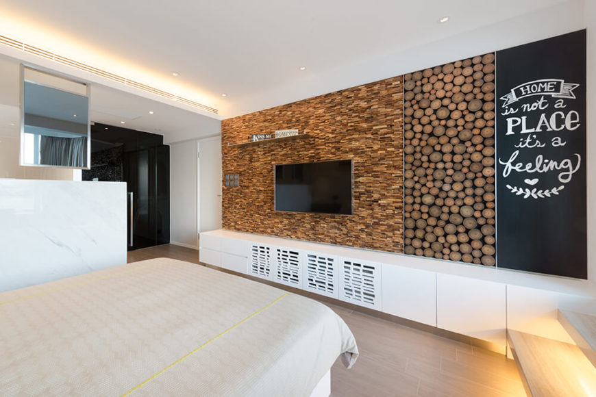 The wall opposite the bed in the master bedroom uses wood tiling, cross sections of trees, and a blackboard to add more texture and interest to the neutral colored room.