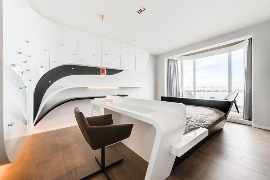 The guest room is outfitted in a simple black and white color scheme and utilizes a set of organic curves, mimicking the flow of air, drawing the eye to the view of the ocean outside the large windows.