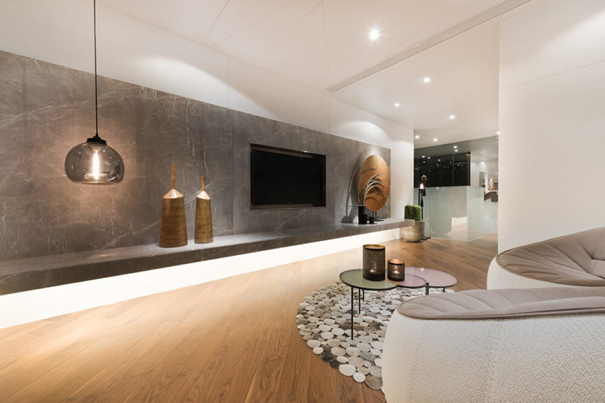 The corridor leading the the bedrooms is also utilized as a small sitting room. The wall is hung with grey marble and supports a large screen TV. The warm wood floors balance the cool grey of the wall and the stone shapes in the rug bring a natural touch to the room.
