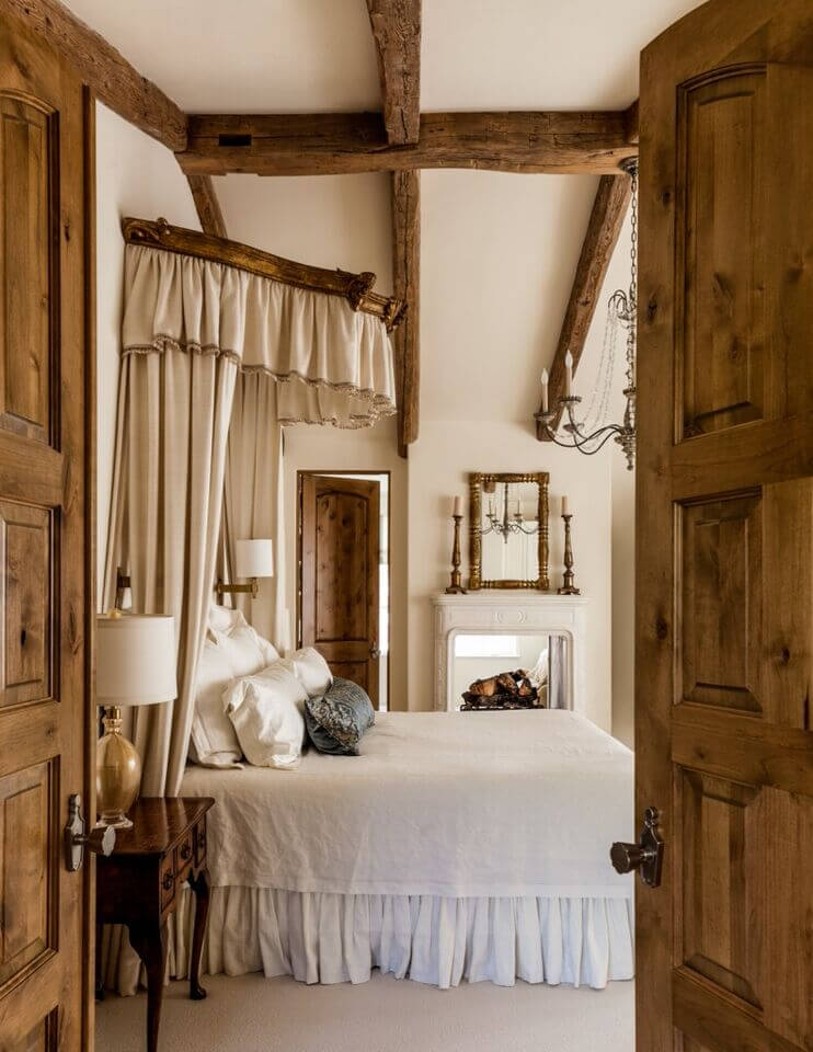 Rustic double doors provide entrance to this lovely traditional master  bedroom with a touch of rustic