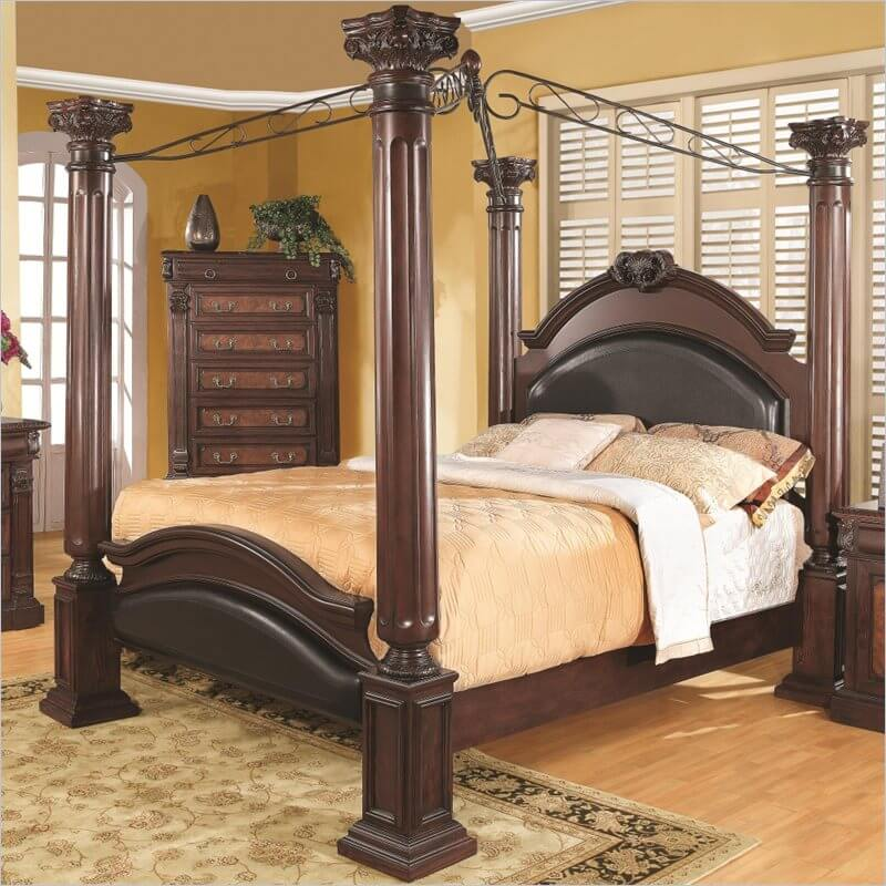 A stately four poster bed in rich dark wood and leather inlays. Wrought  iron bars