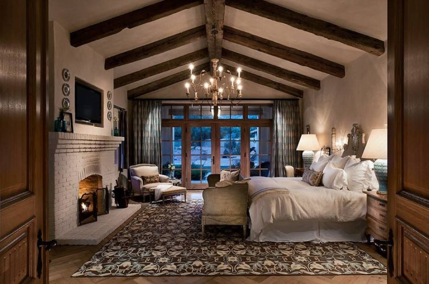 A luxurious bedroom featuring vaulted ceilings, a large chandelier, rich textiles, and complementary earth tones.  The wall mounted television rests above a painted brick fireplace.