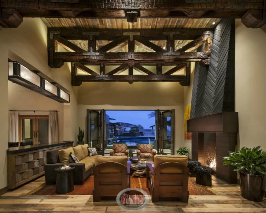 A phenomenal rustic living area incorporates browns, tans, and burgandy to create a space that is truly breathtaking. The dark brown wooden beams of the ceiling preside over the area, while great doors open up to a patio and offer a stunning view of the outside world.