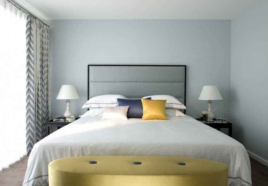 A Minimalist Bedroom With A Chic Colored Headboard, Walls, And Bed Linens  To Create
