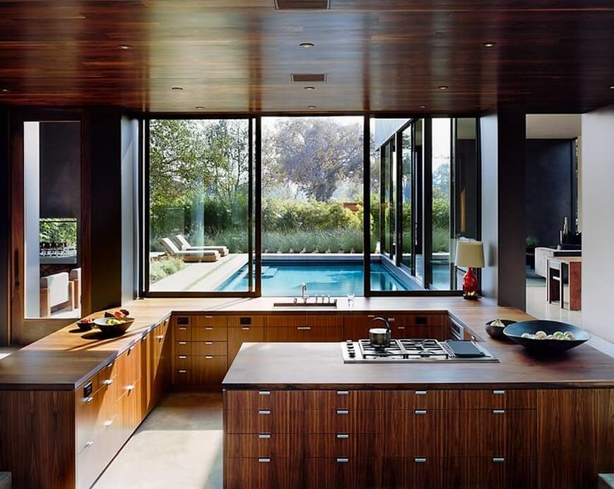 In an elegant room defined by modern shapes and traditional materials, we see rich wood cabinetry and countertops crafted into a sharply angled G-shape. Large windows open to allow a direct connection with the courtyard and adjacent pool. The central nature of this kitchen's placement within the home allows the design to carry extra heft, defining the space within a large open plan.