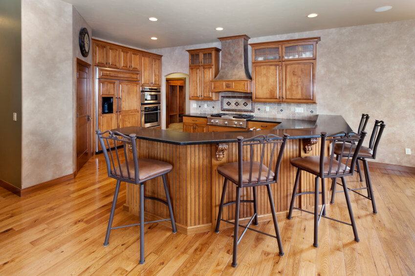 Standing within a larger open-plan space, this kitchen is defined by its G-shaped countertop, wrapping around a broad space with dark countertops and plentiful space for elevated dining. Rich traditionally styled wood cabinetry grounds the room's presence. With the expanse of hardwood flooring beneath this space, the entire package feels coherently styled.