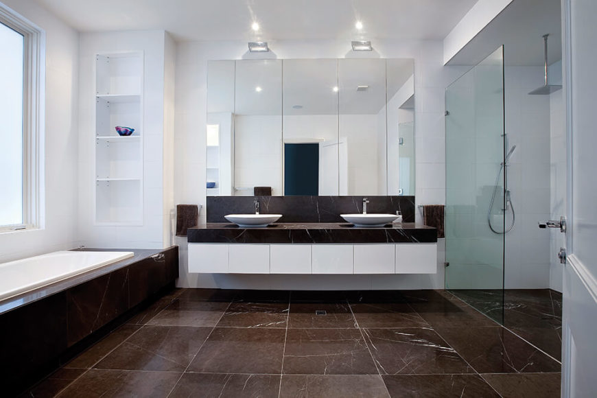 The master bathroom spreads over an expanse of dark marble flooring, with a glass enclosed walk-in shower at right and large soaking tub beneath the window at left. The floating double vanity features white cabinetry and a marble surface supporting a pair of white vessel sinks.
