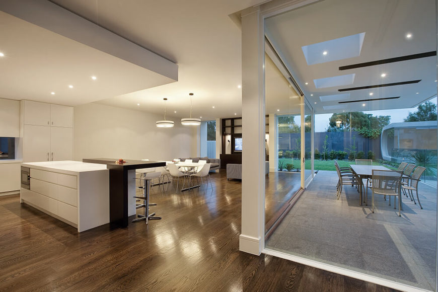 Moving back, we see the full expanse of the open-plan space, wrapped in full height glazing for a truly breathtaking view of the surroundings. The white interior and dark hardwood flooring work in textural contrast to the exterior, awash in light grey concrete and surrounded by greenery.