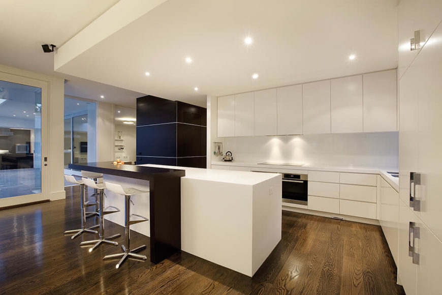 Looking closer at the kitchen, we see the sleek white, hardware-less cabinetry wrapping a minimalist space, defined as much by its drop ceiling with recessed lighting as the large island at center. The island features a raised black surface for in-kitchen dining.