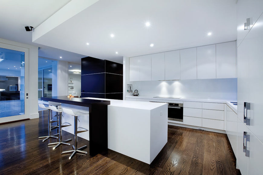 Across from the kitchen, we see a large black wall near the entryway, working like the strip of black in the kitchen island for a high contrast appearance, spiking the expanse of white.