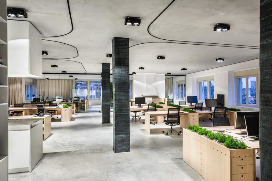 The carbon wrapped pillars add a dose of contrast and help define the structure, standing out amidst rows of bright, warm toned natural wood desks. With the curtains fully opened, the open floor plan feels vast and interconnects the work areas.