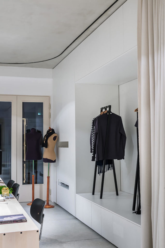 This corner of the office sports more of the sleek white paneling as seen in the kitchen module, providing discreet storage and bright contrast to the concrete flooring.The curtain tracks are the only noticeable feature of the ceiling.