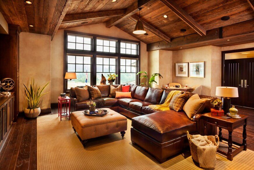 This large leather sectional takes center stage in this expansive living room. Vaulted ceilings in natural wood complement the wood flooring and keep the space from feeling too big.