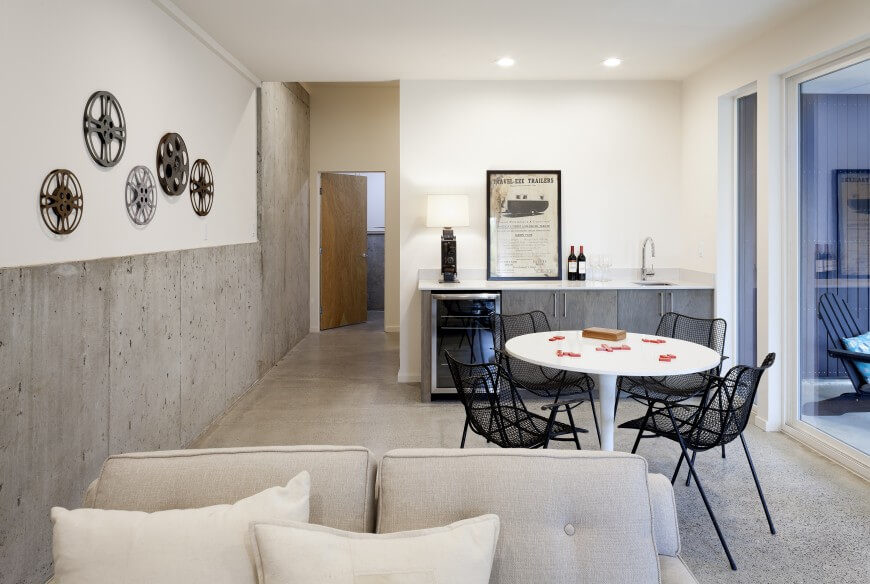Finishing the bottom of the wall with thin slabs on concrete is a great way to maintain a more industrial-chic feel in a room. Black furniture stands out against the light hues of the room. Their mesh construction keeps them from feeling too heavy or appearing too bold in the room, balancing things nicely.