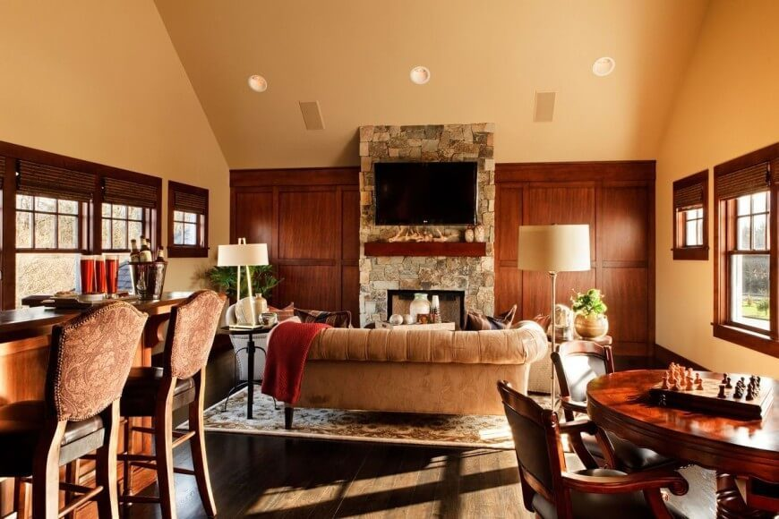 While vaulted ceilings make this room feel large, the seating area is intimate and cozy. A paneled accent wall offsets the the stone fireplace and the plush velvet furniture in soft and inviting.