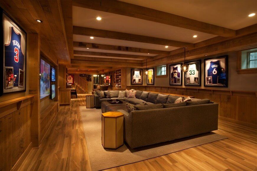 This family room was designed with the intention of hosting sports parties. The huge couch offers plenty of space for seating and is in reach reach of a surface for food or drink. The honey wood used throughout the room warms up the space and helps reflect lots of light, countering the lack of windows in this basement room.