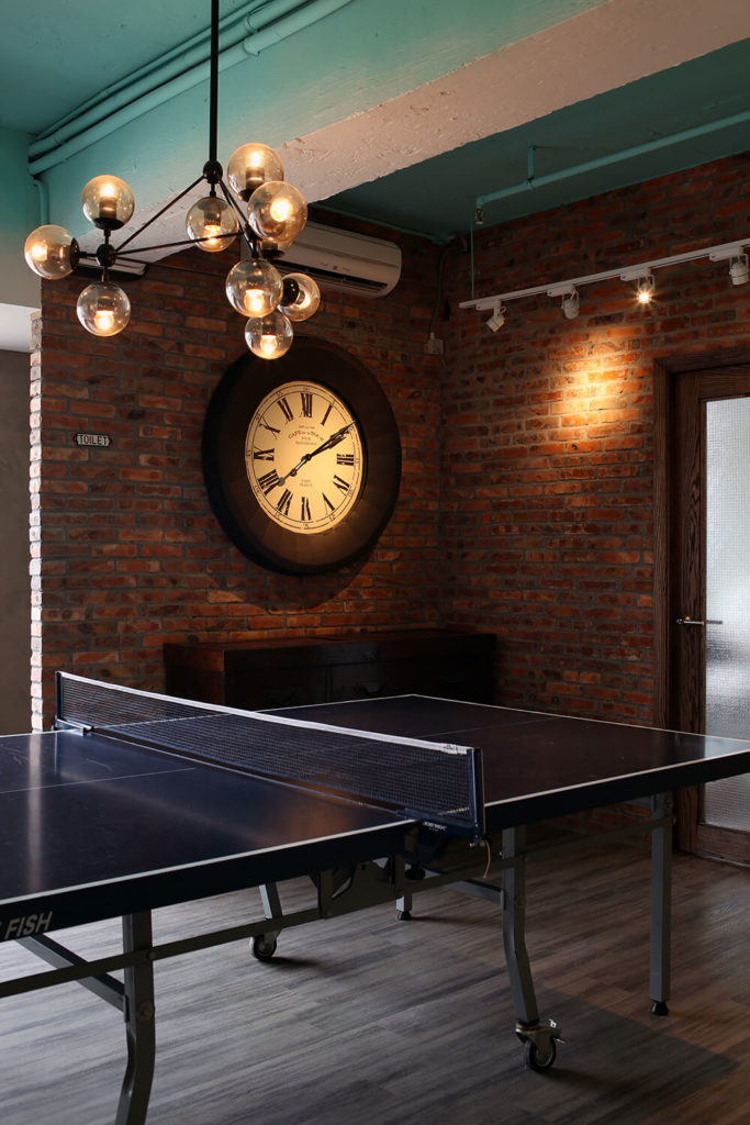 With hardwood flooring and brick walls in this relaxing corner of the office, the environment feels entirely divorced from the bright white and blue space of the main room. A ping pong table highlights the sense of fun inherent in the design.