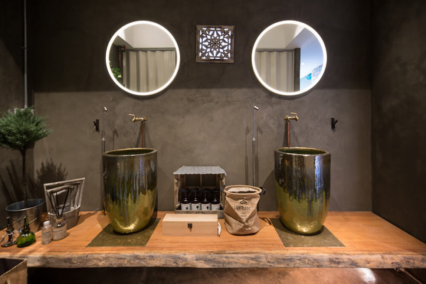 The centerpiece of the bathroom is this floating single slab natural wood vanity that houses a pair of stained metal vessel sinks. The sinks appear in a breathtaking vertically oriented shape, the likes of which we've never seen before.