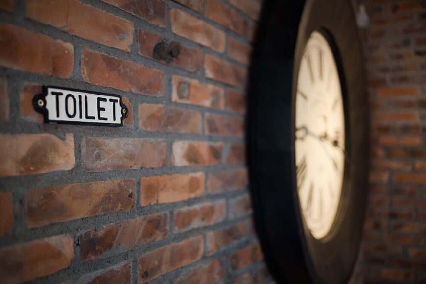 As the old fashioned sign for the bathroom indicates, this area takes a detour through historical style. Red brick walls set the tone, while a large traditional face clock hangs to the right.