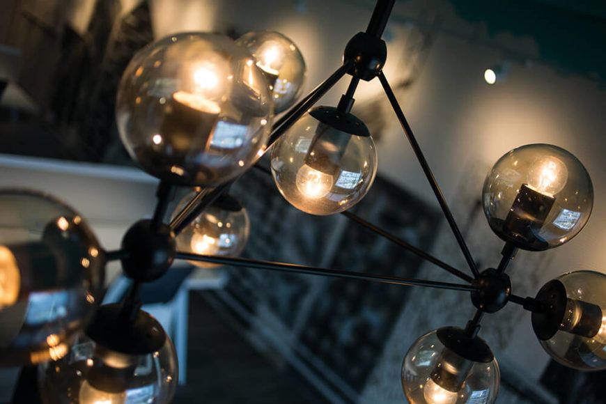 The lighting includes chandeliers like this, featuring an interconnected set of smoked spheres and black metal piping. It turns the traditional notion of a chandelier on its head.