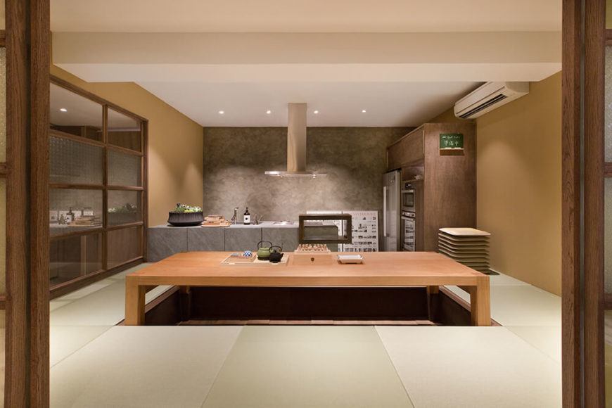 The kitchen area itself centers on a massive natural wood dining table, set into the ground for traditional dining arrangements. The functional half of the kitchen is tucked against the grey wall in the background.