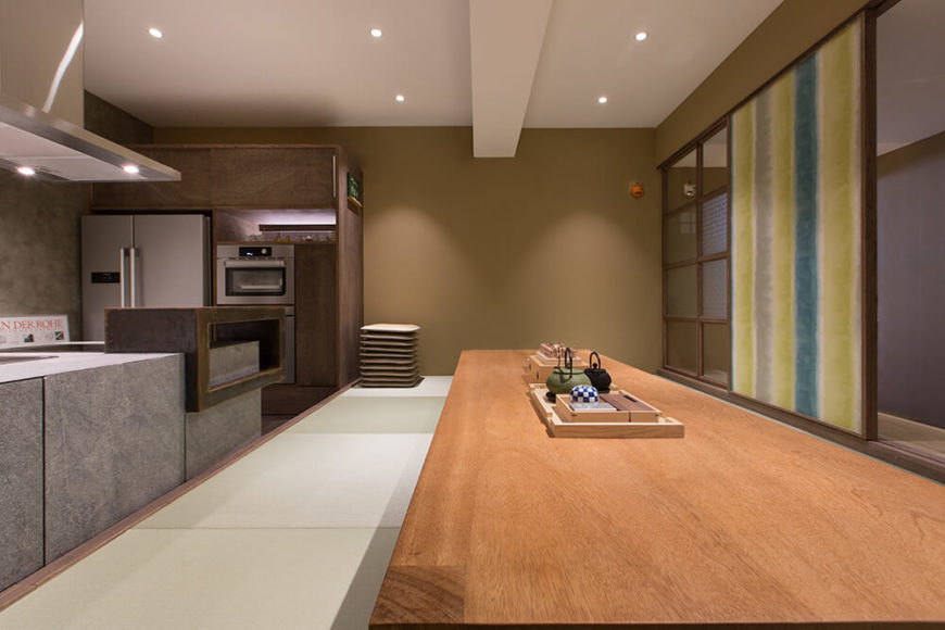 The rich wood of the table and far cabinetry contrasts with the concrete slabs and stainless steel appliances seen at left. Even the shoji wall holds a uniquely painted art panel.