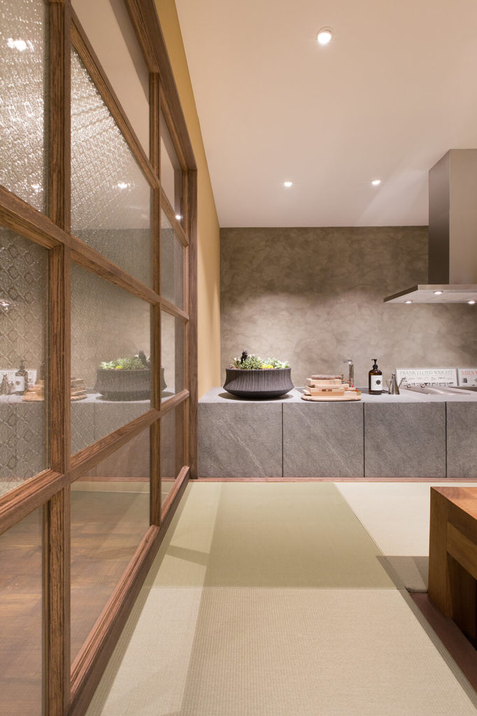 Through the textured glass shoji wall, we can see some of the hardwood flooring in the next room at left. The grey slab countertop helps define the kitchen, distinct from every other space in the office.