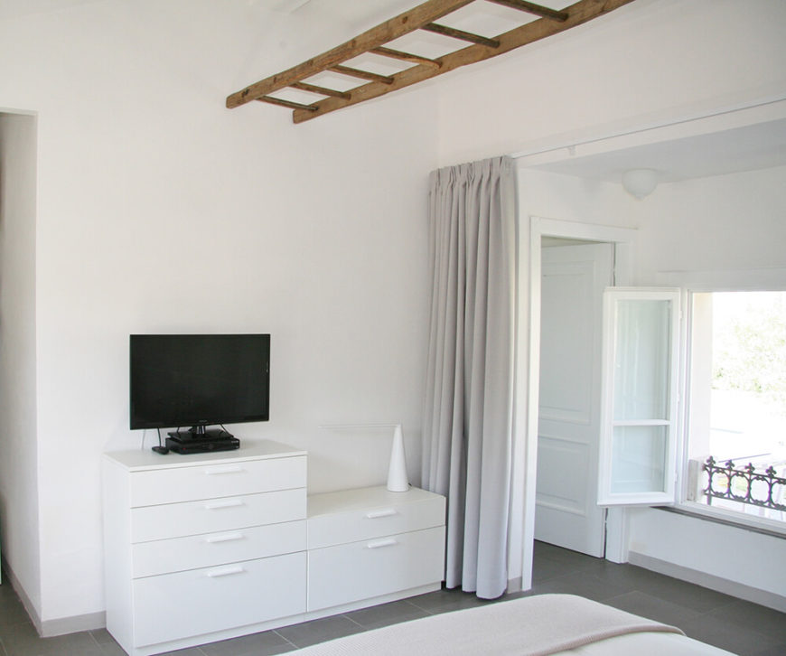 One side of the single bedroom offered in the guest house. Following the minimalist design, everything is basic but comfortable. The room can be sectioned off by curtains to block off the large windows.