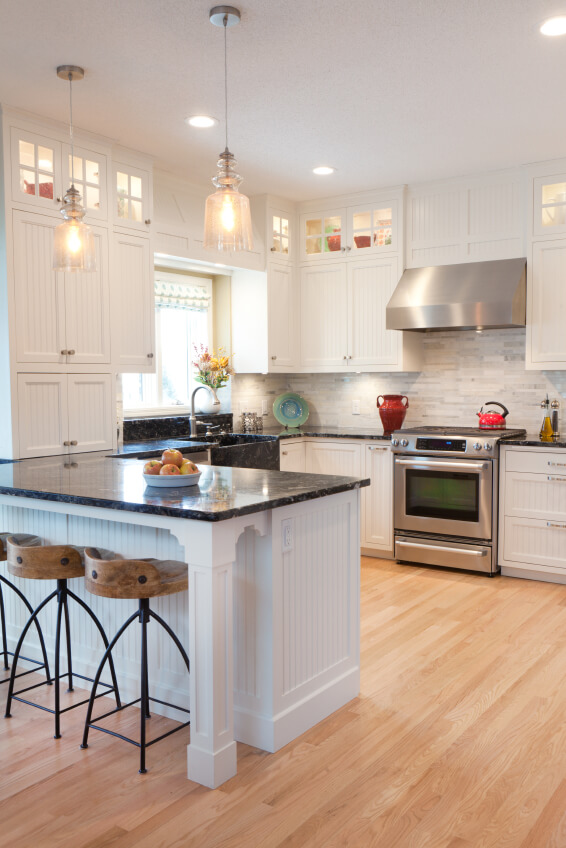The pristine white cabinetry in this kitchen contrasts sharply with black granite countertops, wrapping all around a bright space grounded by hardwood flooring. A light tile backsplash adds texture without disrupting the color palette. The bar stools standing at the countertop add a splash of rustic charm, with dark metal frames and carved wood seats.