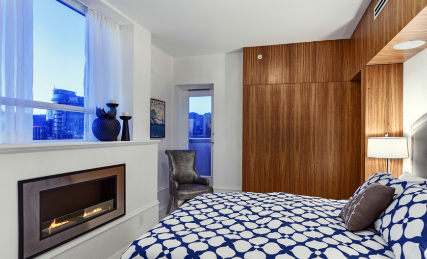One of the two guest bedrooms; this room keeps to the woodwork theme while adding a pop of bright color in the bedspread that is unseen in the rest of the house. A small balcony leads off each side of the room while the fireplace adds a touch warmth. The large window offers more stunning views of the city and landscape.