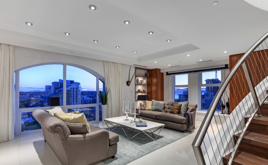 Rich fabrics and bold patterns add more interest to the muted palette while to the right of the room the curved staircase leads up to the second floor. The selective use of stainless steel in the penthouse - the stair railing and the bottom of the coffee table - adds a structural unity throughout the residence.