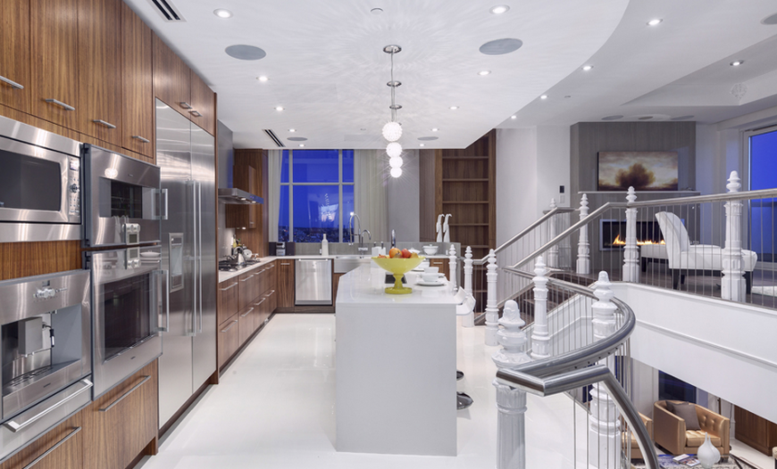 The far end the kitchen offers more counter space and overlooks the open room of the library below. To the left is a better view of the striking appliances set into the cabinets. The pendant lights over the island cast wonderful patterns on the ceiling.