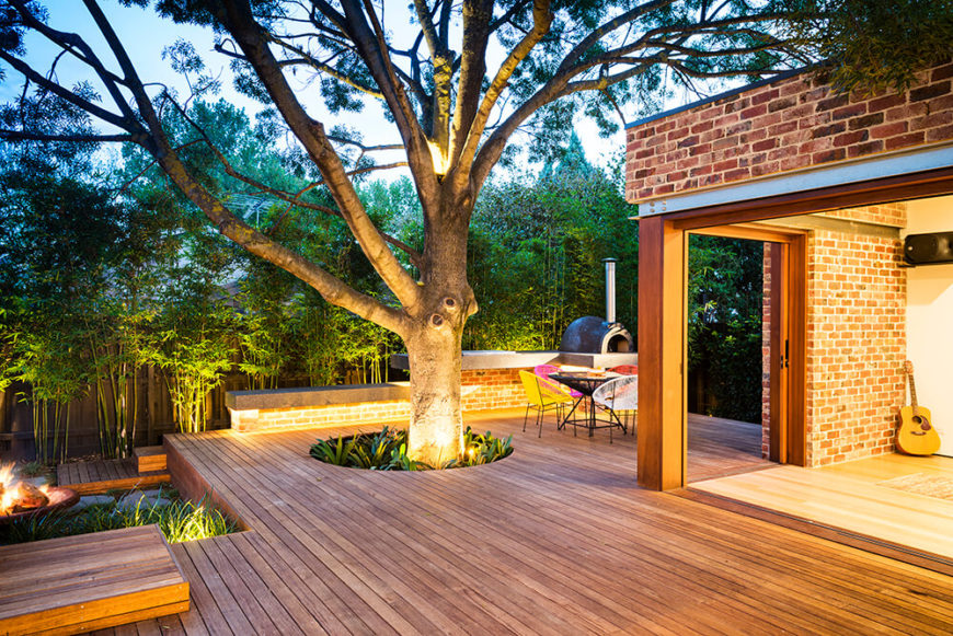 At night, a series of upward facing spotlights illuminate the entire landscape, from the bamboo border to the central tree growing from beneath the deck.