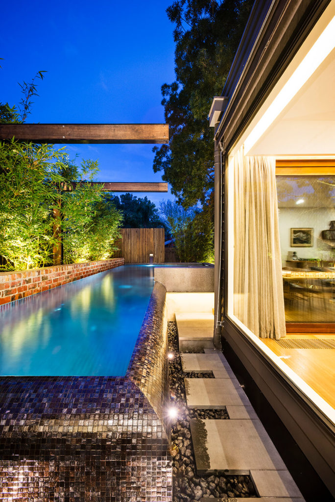 Below the rounded edge of the pool, we see a splashdown layer of stoned next to a slim concrete walkway. The massive windows make enjoyment of the outdoors from inside a regular occurrence.