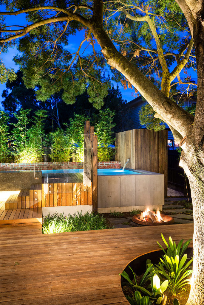 Next to the pool sits a small fire pit, adding another layer of natural delight to the complex outdoor structure.