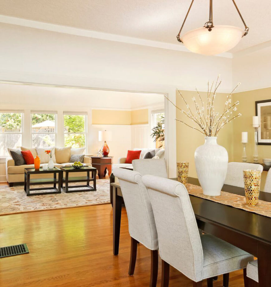 Bright Soft Yellow Walls And Warm Hardwood Flooring Are Contrasted In This Dining  Room By A