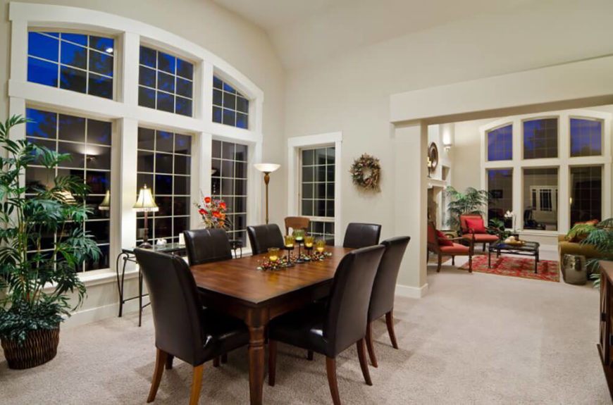 Beneath a soaring arched ceiling, a dark stained wood dining table commands the center of this dining room. Surrounded by black leather upholstered chairs, it injects contrast and interest to the space.