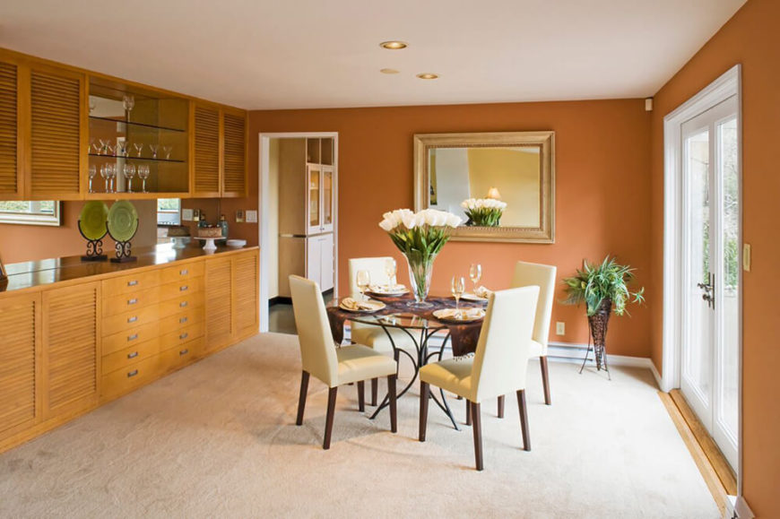 A Soft Burnt Orange Color Surrounds This Dining Room Paired With Light Wood Cabinetry And