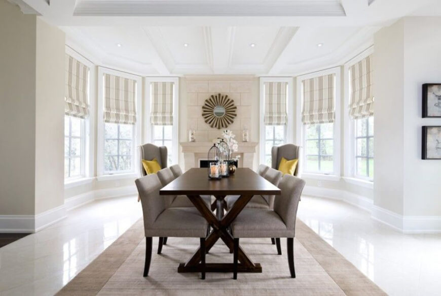 In a stately, broad white space, the dining room centers on a large beige area rug, with dark wood table. The armless dining chairs flanking the table appear in textural beige upholstery, with similarly dark wood legs.