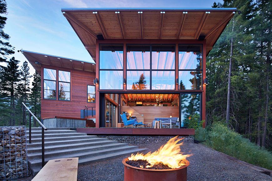 Here is a better view of the patio and fire pit with a lovely view of the back of the house. Understated outdoor lighting keeps the area lit while not detracting from the view or design. The building to the left houses the family room.