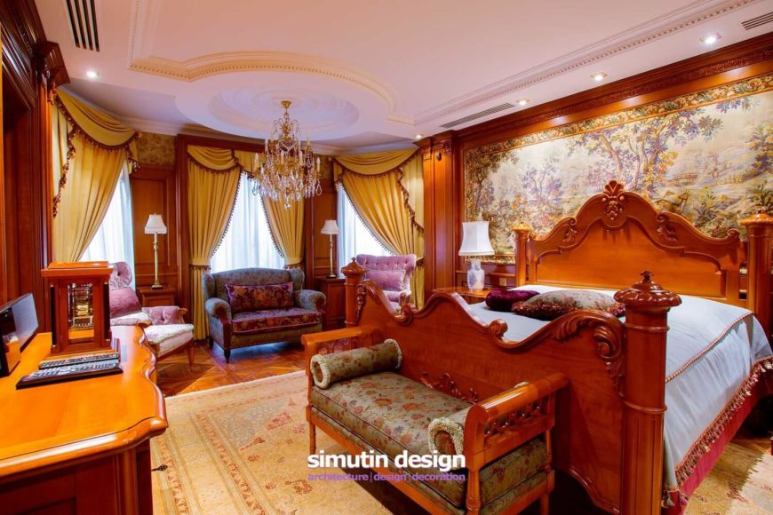 Continuing into the guest suite, we see ornate furniture and architectural details in abundance. The wall behind the headboard is covered in a beautiful mural in more earthy colors than in the rest of the home. A chandelier hangs from a domed ceiling above the large seating area to the left.