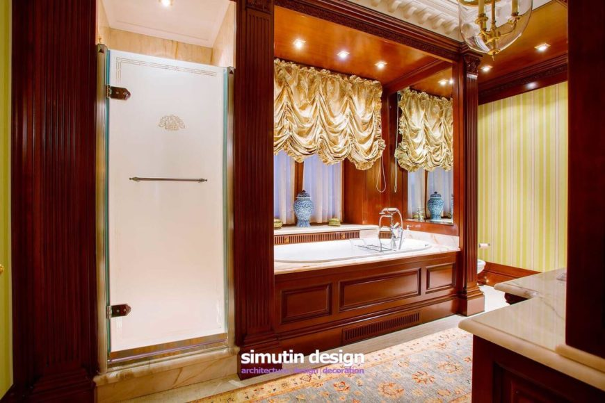 The master bathroom features a steam shower encased in marble, marble countertops and a soaking tub enclosure, and silken, ruched curtains.